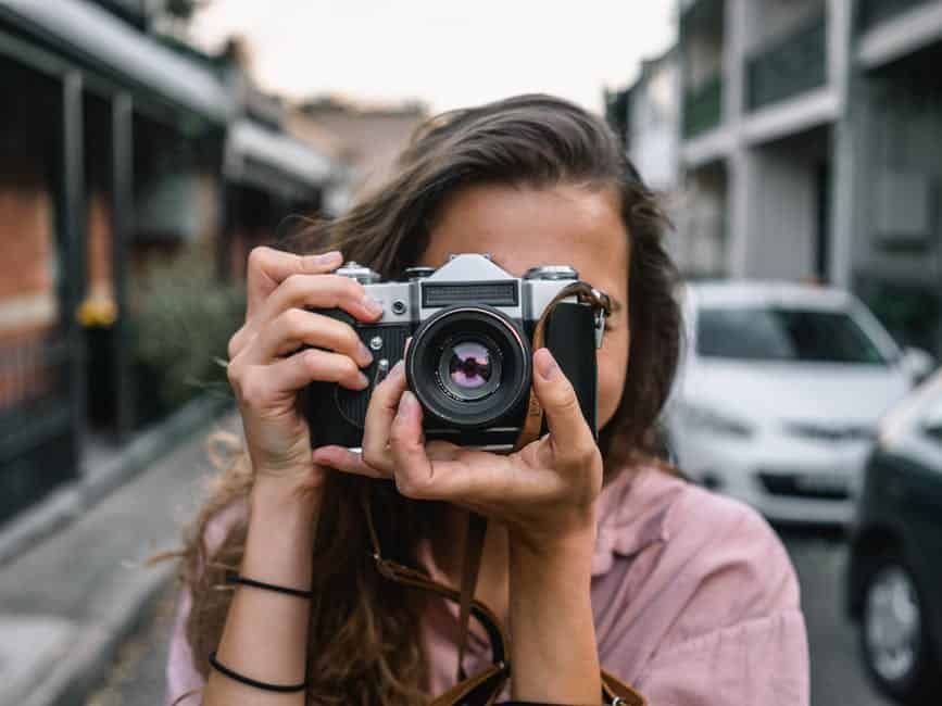 A person holding a camera in front of a building