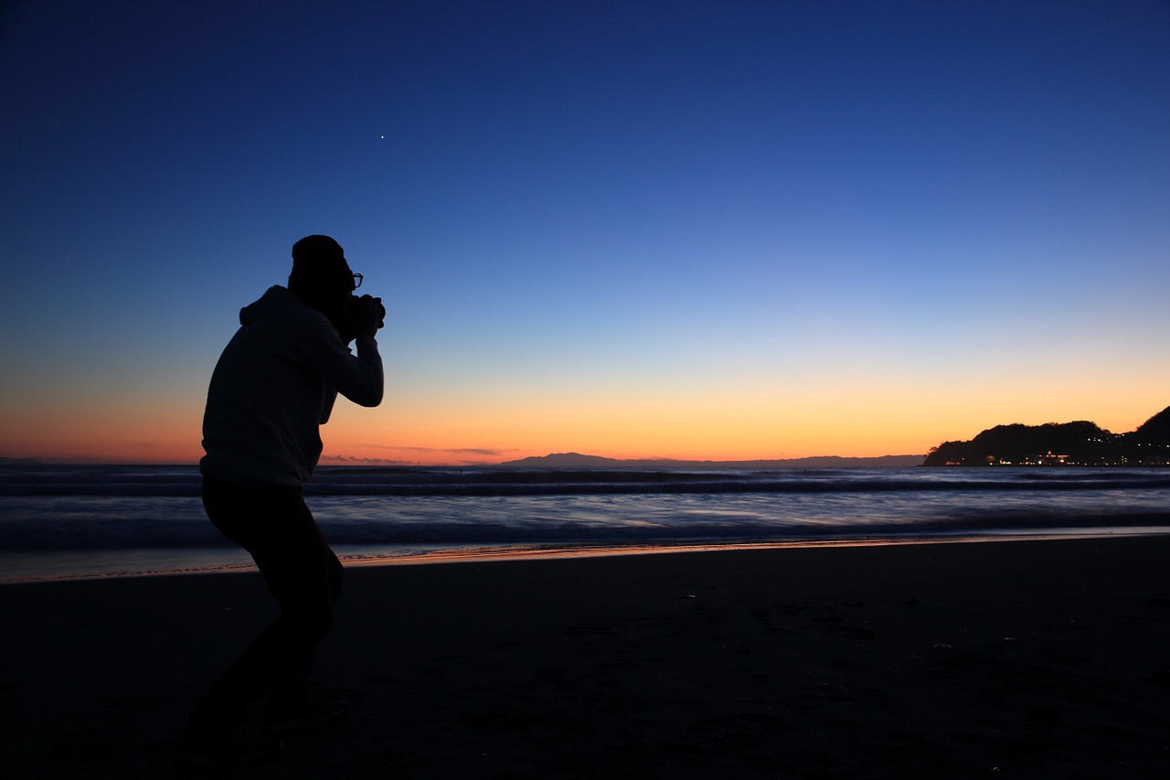 A man standing on a beach with a sunset in the background